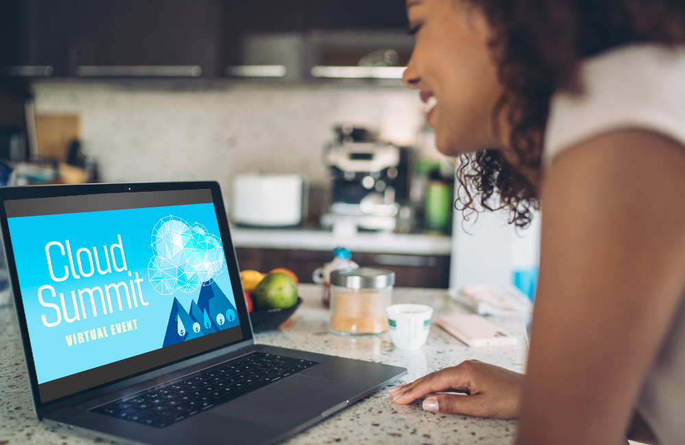 Woman looking at Cloud Summit logo on laptop computer in kitchen