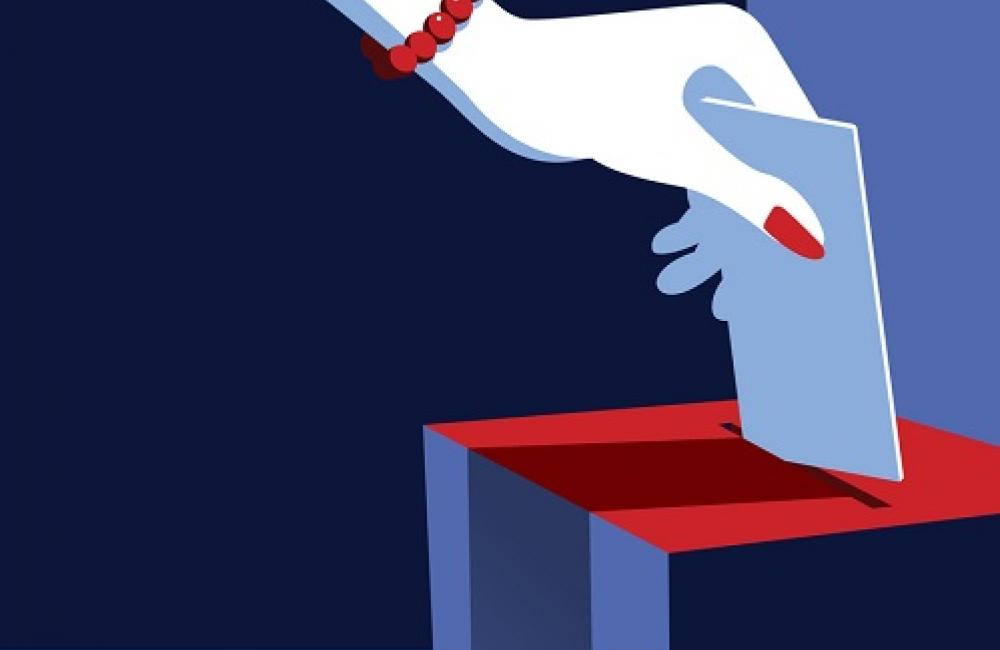 Woman's hand inserts vote into ballot box