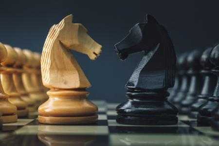 Chess pieces, two knight pieces facing each other.