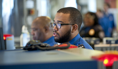 A TSA agent monitors the x-ray machine in the security line at BWI airport